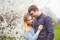 Jeunes couples romantiques se tenant devant le TR de floraison merveilleux Image stock