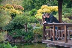 Jeunes couples romantiques se tenant sur le pont regardant sur l'eau Photos libres de droits