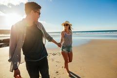 Jeunes couples romantiques tenant des mains et marchant sur la plage Photo libre de droits