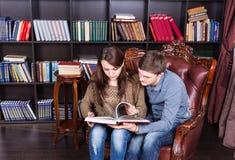 Jeunes couples sérieux sur une chaise lisant un livre Photo libre de droits