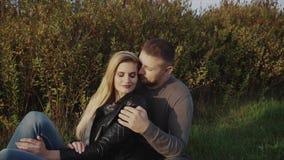 Jeunes couples s'amusant s'asseyant sur la pelouse en parc d'automne clips vidéos