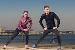 Jeunes couples s'exerçant au bord de mer Photo stock
