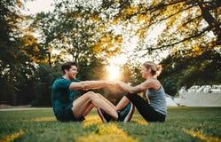 Jeunes couples s'exerçant ensemble au parc Image libre de droits