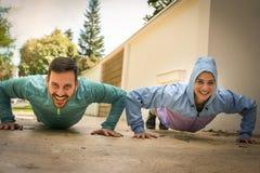 Jeunes couples s'exerçant ensemble sur le trottoir Image libre de droits