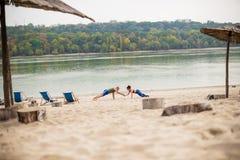 Jeunes couples s'exerçant sur la plage Image stock