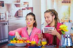 Jeunes couples sains hispaniques appréciant le petit déjeuner ensemble, partageant des fruits et souriant tout en regardant l'écr Photographie stock