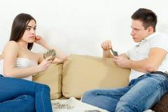 Jeunes couples sceptiques se trichant dans le jeu de carte Image stock