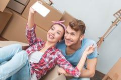 Jeunes couples se déplaçant à la nouvelle femme d'endroit dans la boîte prenant des selfies avec le sourire de l'homme heureux photos stock