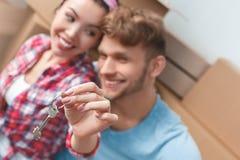 Jeunes couples se déplaçant au nouvel endroit se reposant jugeant le fond brouillé en gros plan de clés gai images libres de droits