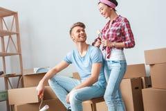 Jeunes couples se déplaçant au nouvel homme d'endroit avec le rouleau de peinture se reposant sur la boîte riant regardant la pos image libre de droits