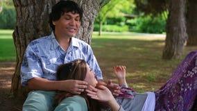 Jeunes couples se penchant contre l'arbre banque de vidéos