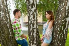 Jeunes couples se penchant sur des arbres et regardant l'un l'autre dans un pair Photographie stock