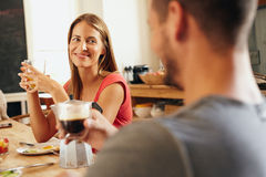 Jeunes couples se reposant à la table de petit déjeuner Photos stock