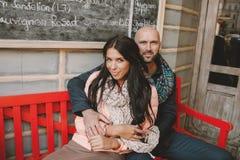Jeunes couples se reposant au banc rouge près du café dans la ville Photographie stock libre de droits
