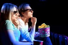 Jeunes couples se reposant au cinéma, observant un film Photographie stock