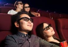 Jeunes couples se reposant au cinéma, observant un film Image libre de droits