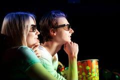 Jeunes couples se reposant au cinéma, observant un film Photos libres de droits
