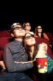 Jeunes couples se reposant au cinéma, observant un film Photo stock