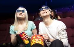 Jeunes couples se reposant au cinéma, observant un film Photo libre de droits