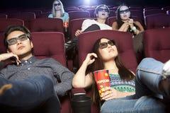 Jeunes couples se reposant au cinéma, observant un film Image stock