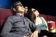 Jeunes couples se reposant au cinéma, observant un film Photos stock