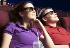 Jeunes couples se reposant au cinéma, observant un film Images libres de droits