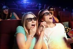 Jeunes couples se reposant au cinéma, observant un film d'horreurs Images stock
