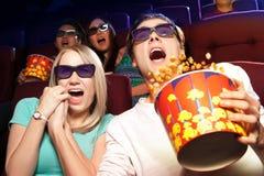 Jeunes couples se reposant au cinéma, observant un film d'horreurs Photo stock