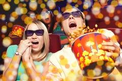Jeunes couples se reposant au cinéma, observant un film d'horreurs Photographie stock