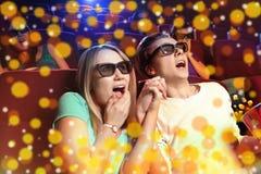 Jeunes couples se reposant au cinéma, observant un film d'horreurs Photographie stock libre de droits