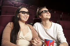 Jeunes couples se reposant au cinéma portant les lunettes 3d, observant Photo stock