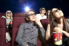 Jeunes couples se reposant au cinéma portant les lunettes 3d, observant Photographie stock