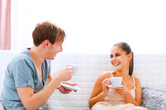 Jeunes couples se reposant au divan et au café potable Photos libres de droits