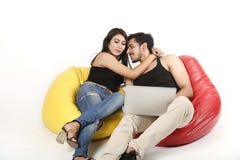 Jeunes couples se reposant avec l'ordinateur portable photographie stock