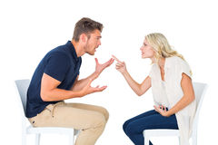 Jeunes couples se reposant dans l'argumentation de chaises Photos stock