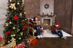 Jeunes couples se reposant dans la chambre avec l'arbre de Noël et serfing Images stock