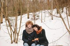 Jeunes couples se reposant dans la forêt d'hiver ensemble Photographie stock libre de droits
