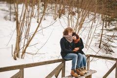 Jeunes couples se reposant dans la forêt d'hiver ensemble Images stock