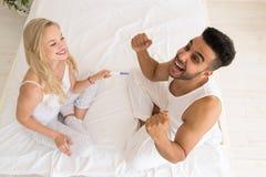 Jeunes couples se reposant dans le lit, essai de grossesse positif étonné criard enthousiaste d'homme de sourire d'exposition heu Photos libres de droits