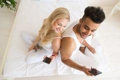 Jeunes couples se reposant dans le lit, l'homme de sourire heureux et la femme hispaniques à l'aide du téléphone intelligent de c Photos stock