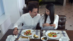 Jeunes couples se reposant dans le restaurant et prenant des photos de la nourriture avec le téléphone portable banque de vidéos