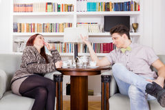 Jeunes couples se reposant dans les chaises dans le salon photographie stock libre de droits