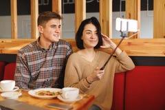Jeunes couples se reposant dans un café Une fille fait un selfie avec un type inside Images stock