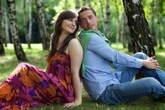 Jeunes couples se reposant de nouveau au dos en parc Photo libre de droits