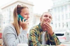 Jeunes couples se reposant en café avec l'ordinateur portable et le téléphone portable, l'homme confus et la femme parlant au tél Photo stock