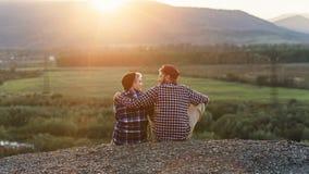 Jeunes couples se reposant en haut de la montagne et regardant l'un l'autre le coucher du soleil Couples doux au coucher du solei photo libre de droits