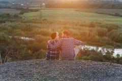 Jeunes couples se reposant en haut de la montagne et regardant l'un l'autre le coucher du soleil Couples doux au coucher du solei photo stock