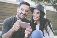 Jeunes couples se reposant en parc de ville Image stock