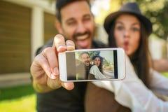 Jeunes couples se reposant en parc de ville Photo libre de droits