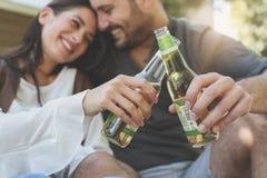 Jeunes couples se reposant en parc et tenant la bouteille de la boisson Photo libre de droits